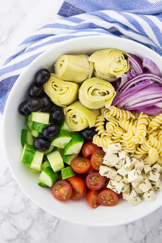 ingredients combined for the Greek pasta salad in a bowl without dressing in preparation of the salad