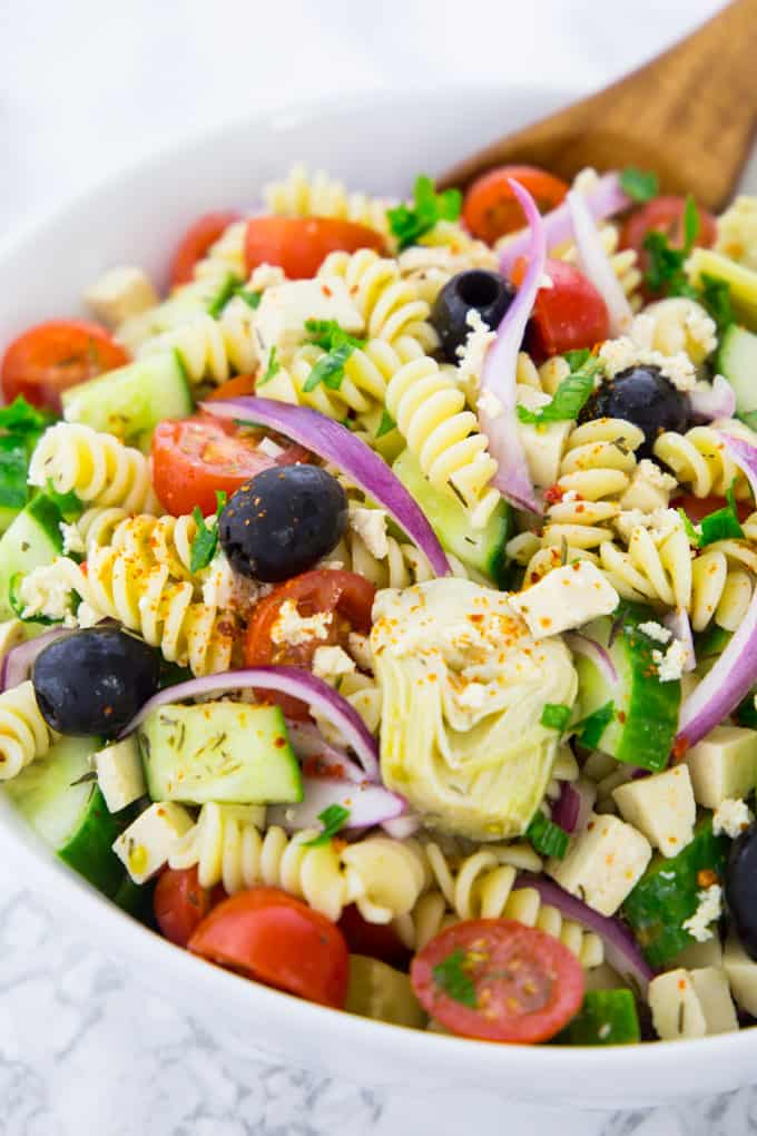 close-up of Greek pasta salad with red onions, olives, cucumber, artichokes, and tomatoes