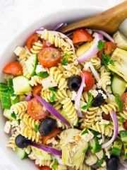 Greek Pasta Salad in a Bowl with a Salad Server