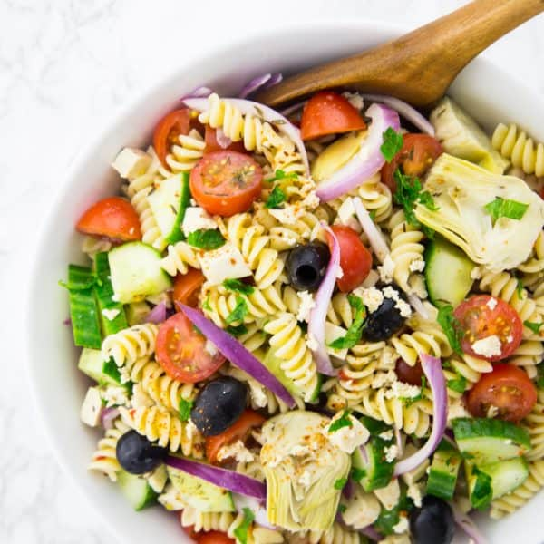 Greek pasta salad with cherry tomatoes, cucumber, olives, red onion, and artichokes