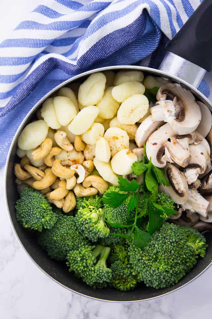 Uncooked gnocchi, mushrooms, broccoli, cashews, and parsley in a pot