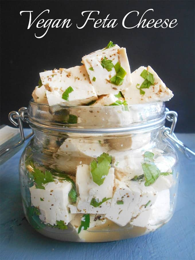 "vegan feta cheese cubes in a glass jar with a black background and the writing ""vegan feta cheese"""