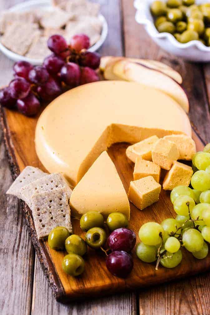 Vegan cheddar cheese on a wooden board with crackers, grapes, and olives on the side