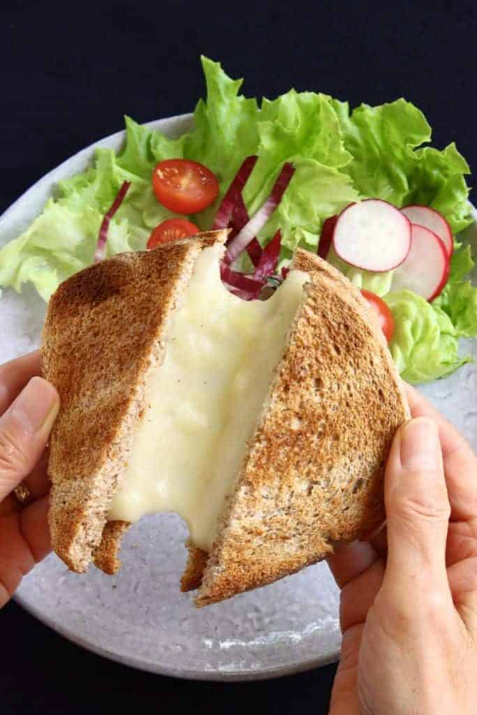 someone holding two halves of a vegan cheese sandwich over a plate with a salad with melted cheese between both halves