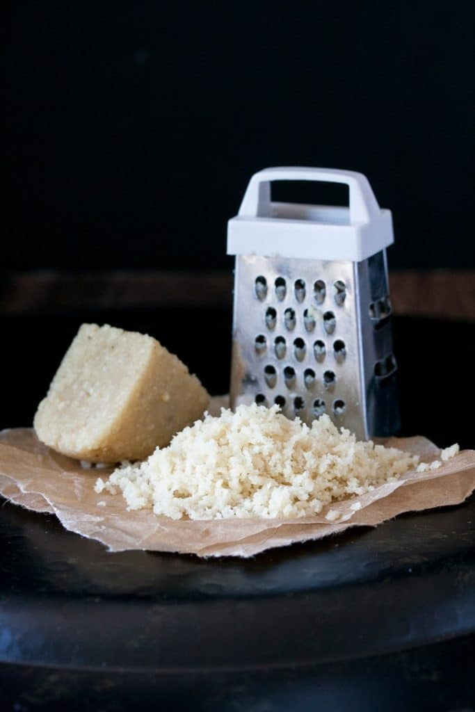 a piece of vegan Parmesan cheese with a tiny cheese grater on a black surface with a black background