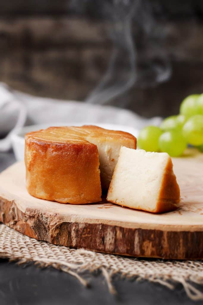 a piece of hickory smoked vegan cheese on a wooden board with grapes and smoke in the background