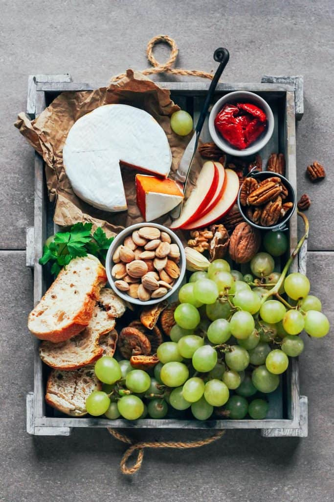 Vegan sun-dried tomato camembert in a wooden tray with nuts, bread, apple slices, and crapes