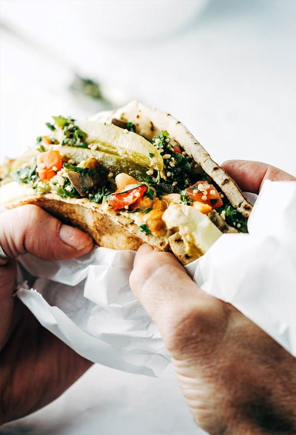 Two hands holding a sabich sandwich