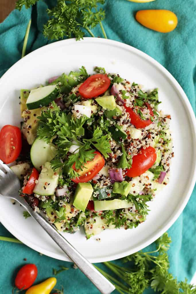 Mediterranean Quinoa Salad on a white plate with a fork on the side