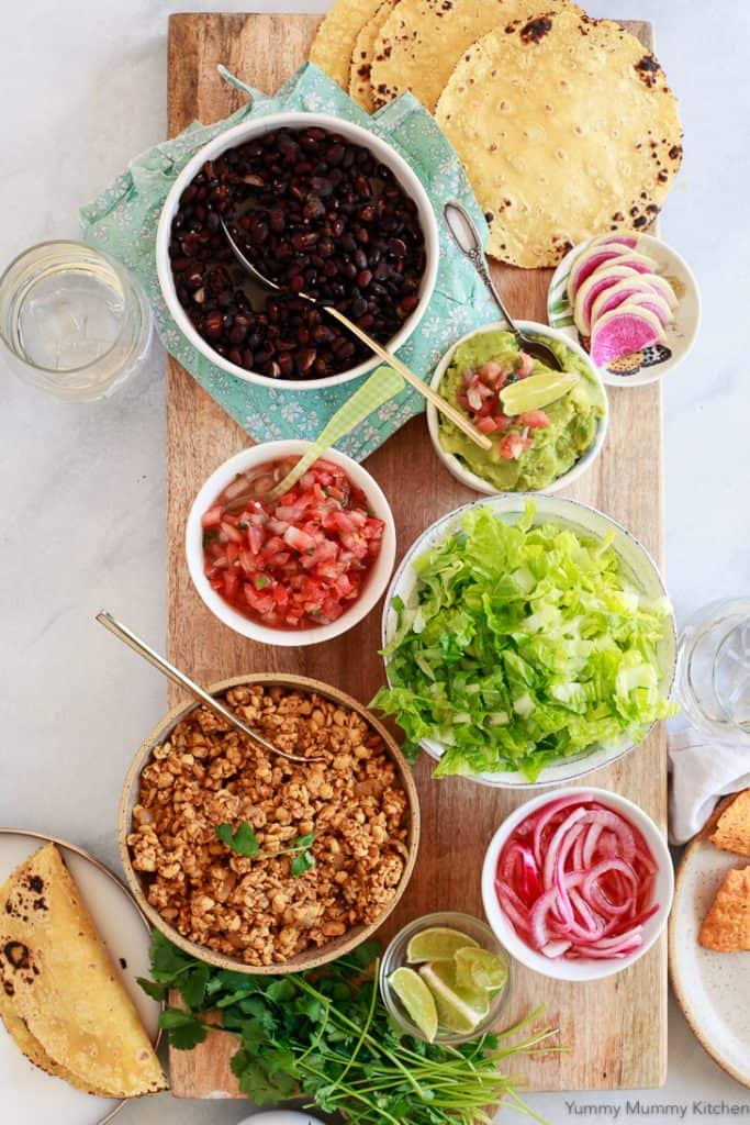 Ingredients for Tempeh Tacos in Different Bowls with Tortillas on the Side