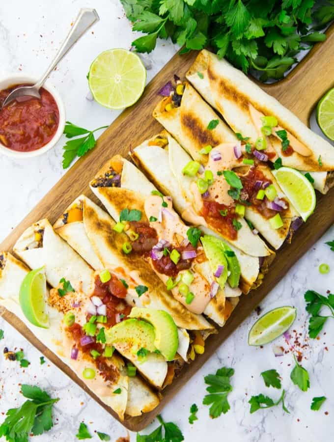 Vegan taquitos on a wooden board with salsa and fresh cilantro on the side