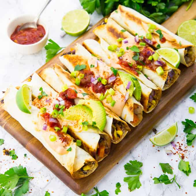 vegan taquitos on a wooden board with salsa on the side