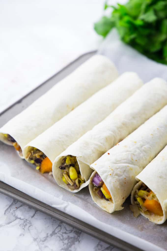 rolled-up taquitos on a baking sheet lined with parchment paper before baking