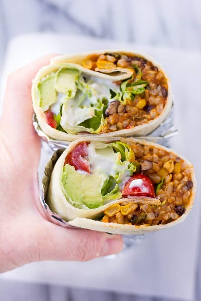 A Hand Holding Two Vegan Burritos
