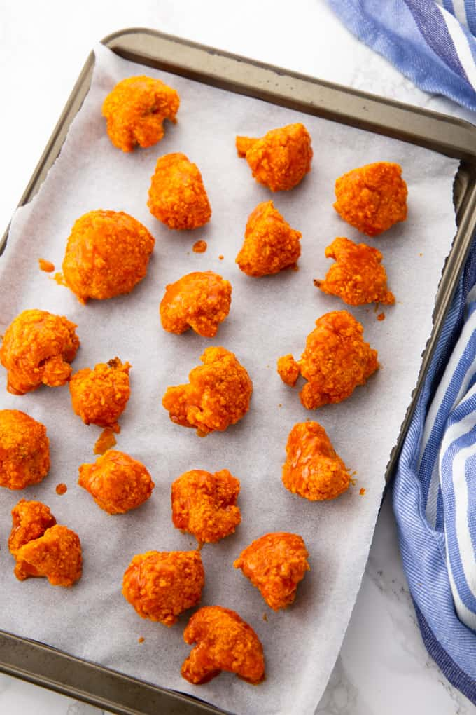 Coated Cauliflower Buffalo Wings on a Baking Sheet