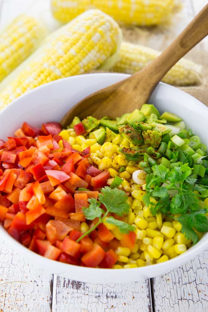 Diced red bell pepper, corn, and avocado in a bowl with a wooden spoon