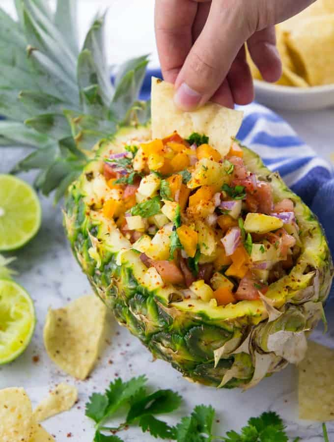 A Hand Dipping a Tortilla Chip into Pineapple Salsa in a Pineapple