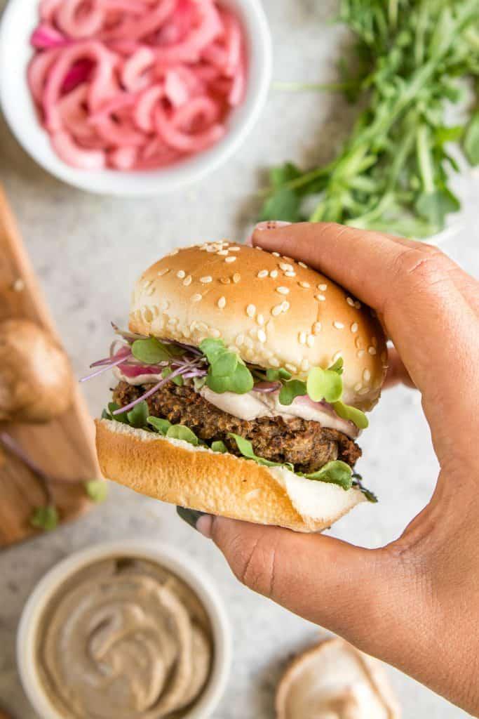 A Hand Holding a Mushroom Veggie Burger