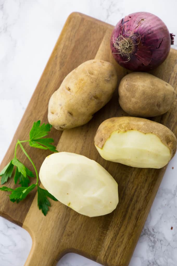 Peeled Potatoes on a Wooden Board