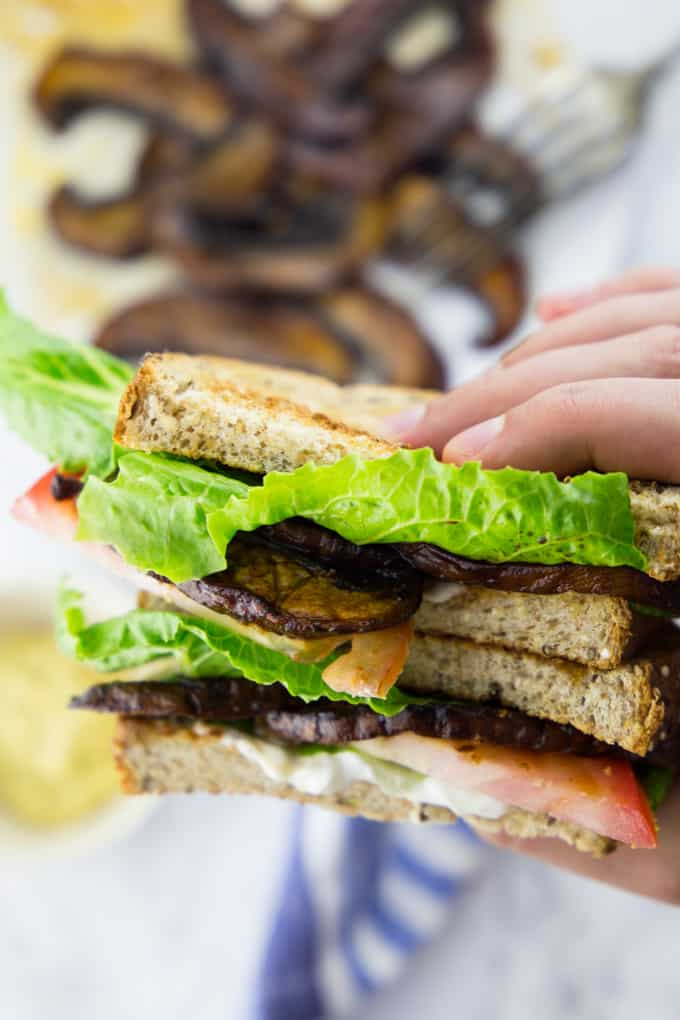 A hand holding a sandwich with vegan mushroom bacon, tomatoes, and lettuce