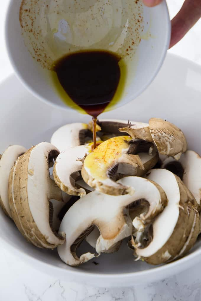 The marinade is being poured over the sliced mushrooms in a bowl