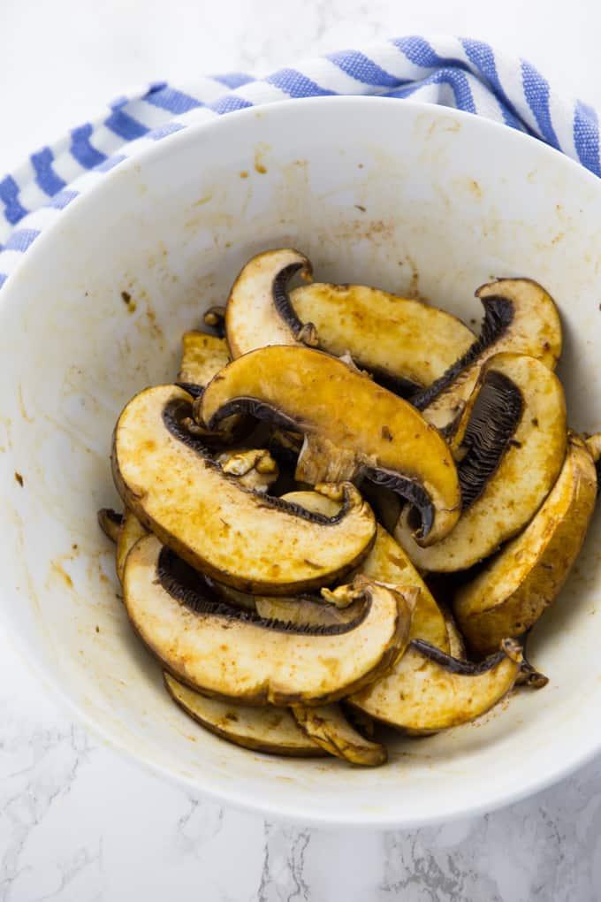 Marinated sliced portobello mushrooms in a bowl