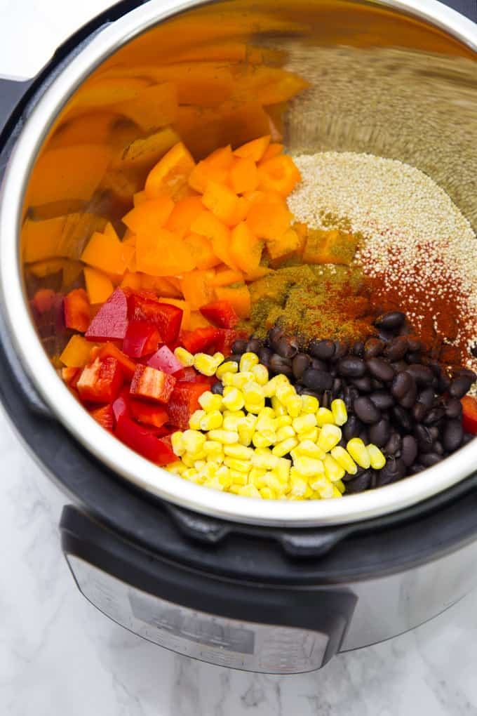 Uncooked quinoa, black beans, corn, and bell peppers in an instant pot