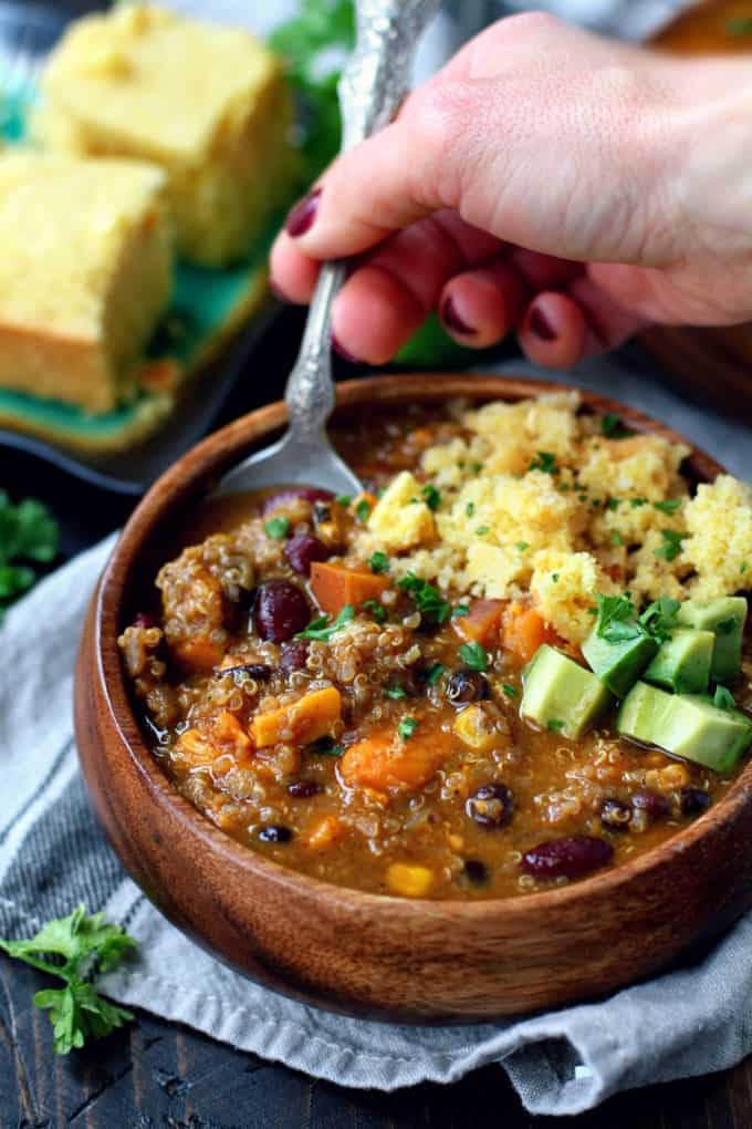 A hand with a fork in a wooden bowl of vegan quinoa chili with couscous on the side