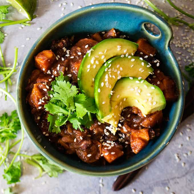 Sweet Potato White Bean Chili in a Blue Bowl with Sliced Avocado, Sesame Seeds, and Fresh Cilantro on Top