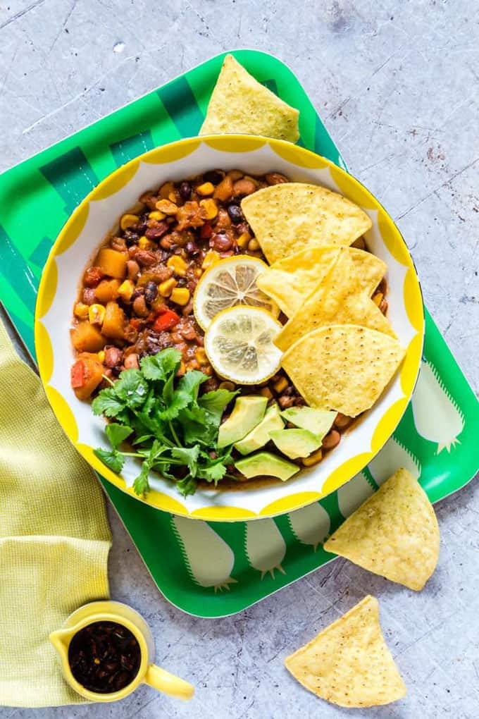 slow cooker vegan chili in a yellow bowl on a green tray with tortilla chips on the side