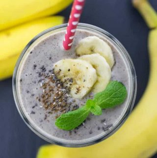 A glass of banana smoothie with a red straw and chia seeds on top on a black counter top