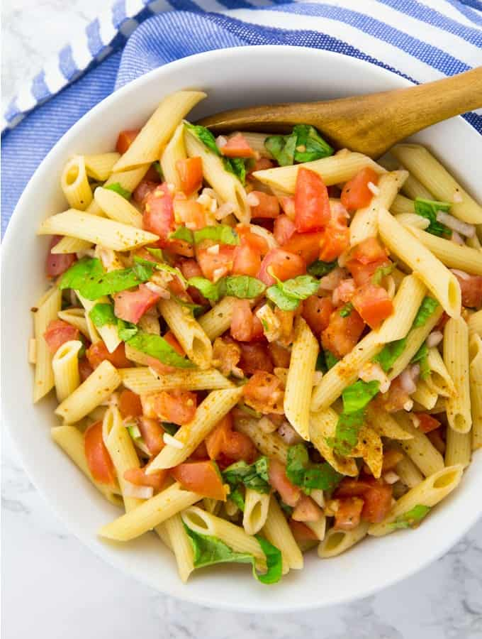 easy pasta salad with tomatoes and basil in a white bowl on a marble counter top with a blue napkin