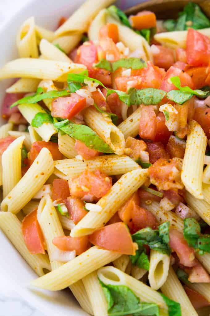 close-up of an easy pasta salad with tomatoes and basil in a white bowl