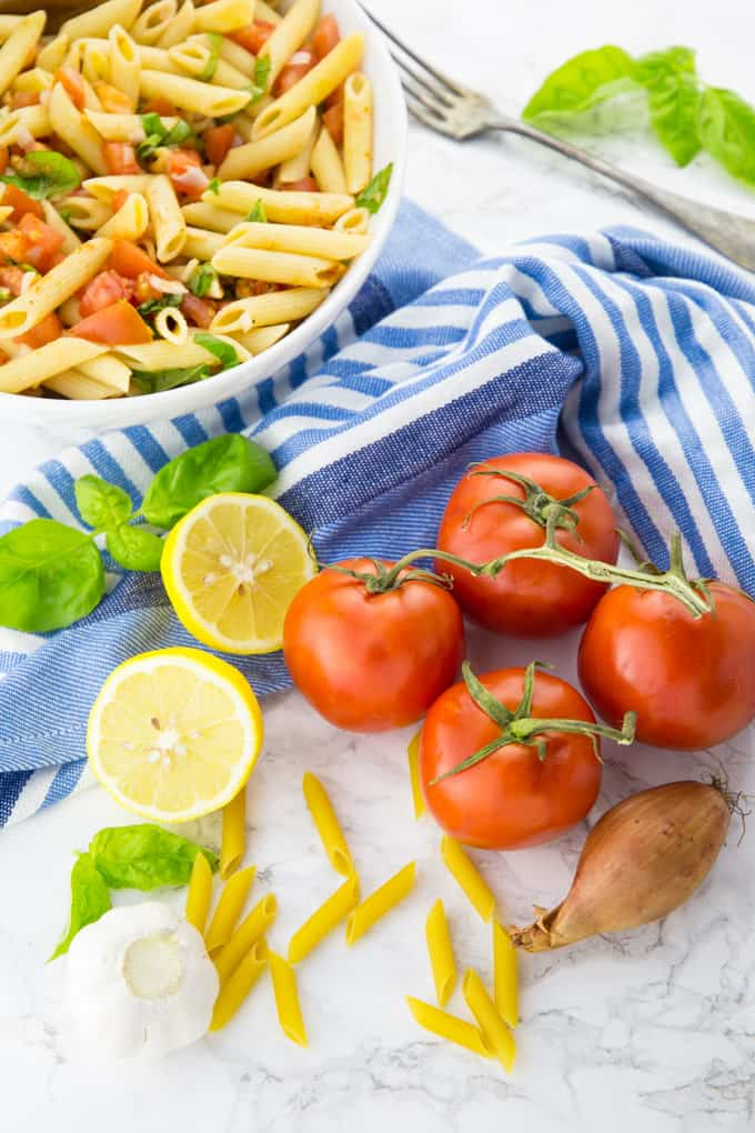 tomatoes, garlic, lemon, shallot, and basil on a marble counter top with a bowl of pasta salad in the background