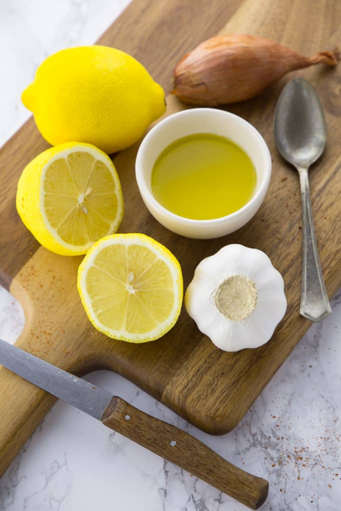 a small bowl of olive oil, two lemons, one clove of garlic, and a shallot on a wooden chopping board