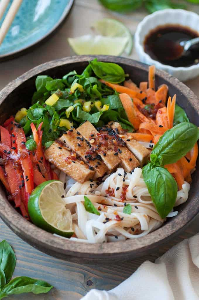 Chilled Smoked Tofu Sesame Rice Noodle Salad in a wooden bowl with soy sauce and lime wedges in the background