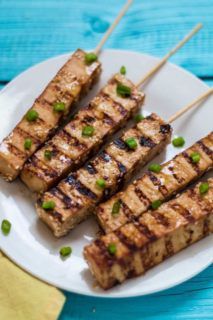five tofu skewers on a white plate on a blue wooden surface with green onions sprinkled on top