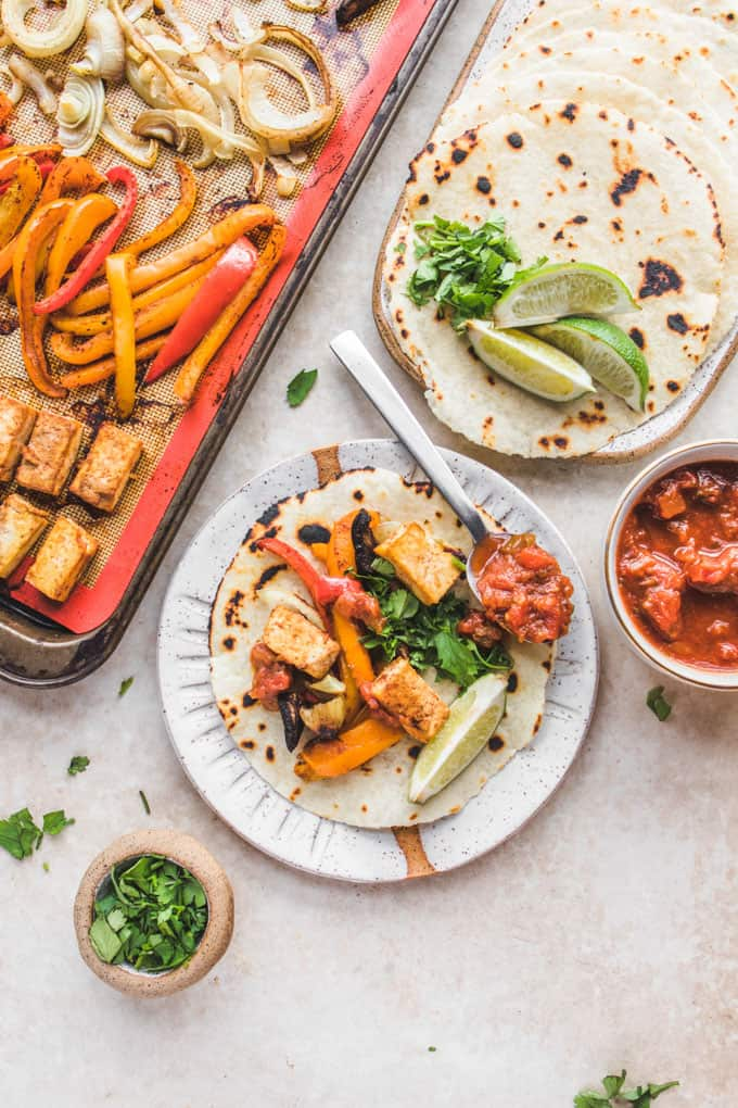 a sheet pan with fajitas and chipotle tofu with two plates on the side with tortillas and lime