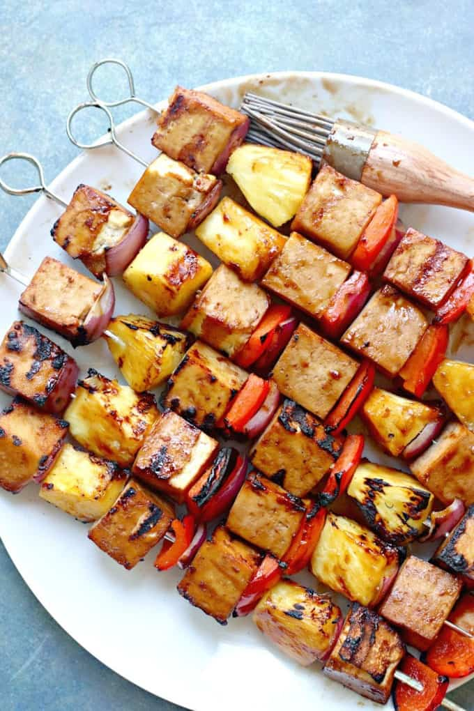 six tofu kabobs one a plate with a pastry brush on a blue countertop