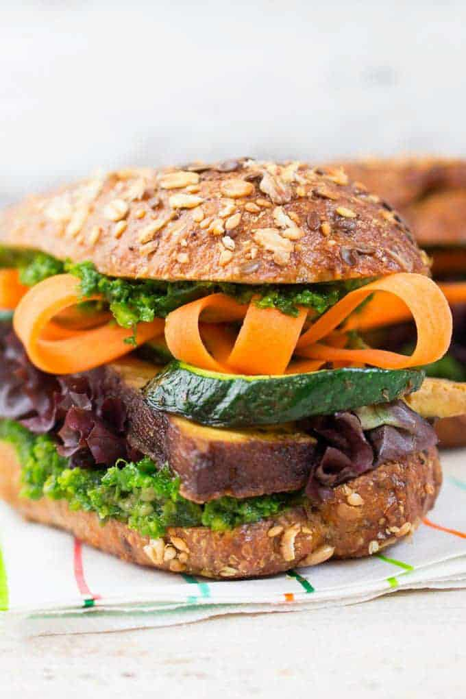 a sandwich with sliced carrots, smoked tofu, and kale pesto on a wooden white counter top