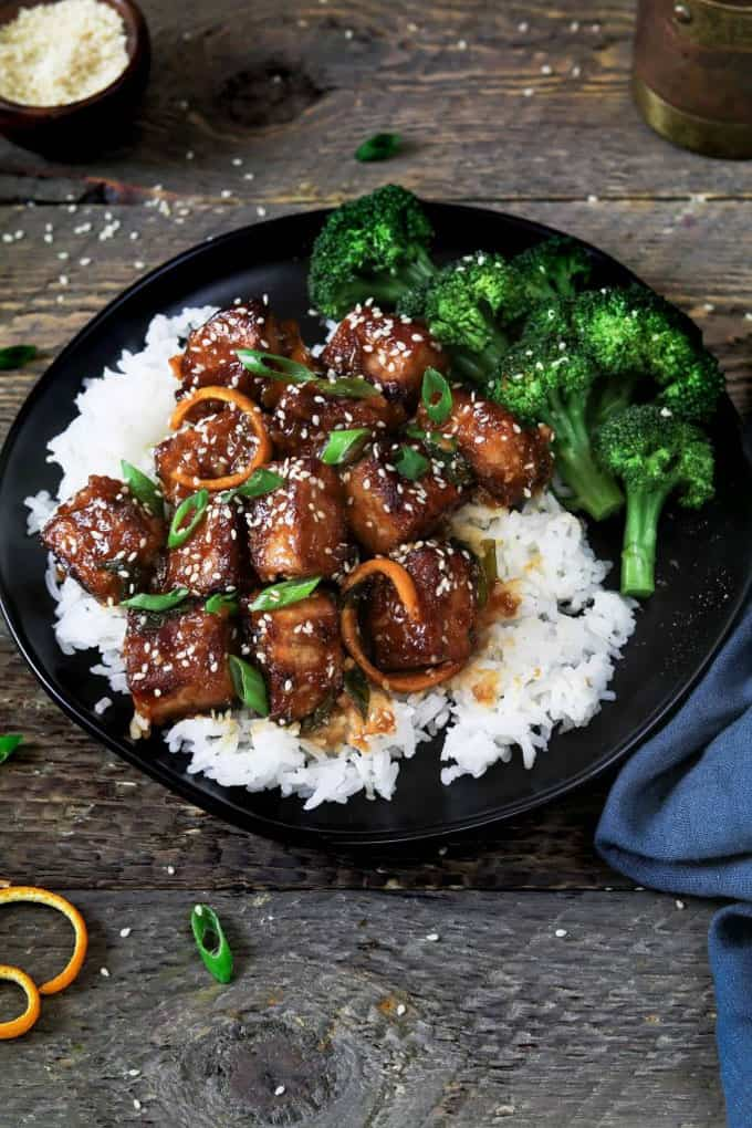 General Tsos Tofu with rice and broccoli in a black bowl on a dark wooden counter top