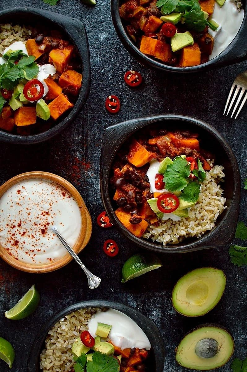 Three Bowls of Sweet Potato Black Bean Chili on a Black Surface with Avocado and a Bowl of Yogurt Sauce on the Side