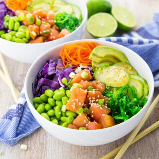 Two vegan poke bowls on a wooden counter top with limes and chop sticks on the side