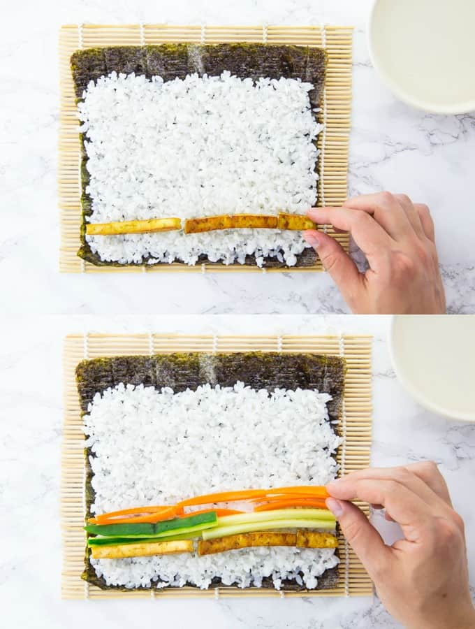thin strips of carrot, cucumber, avocado, and tofu are being placed on a nori sheet with rice
