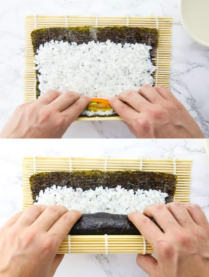 a nori sheet with filling is being rolled on a bamboo mat