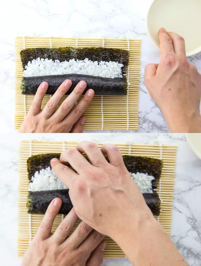 a vegan sushi roll is being rolled on a bamboo mat