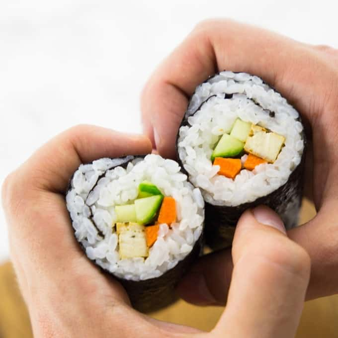 a hand holding two vegan sushi rolls