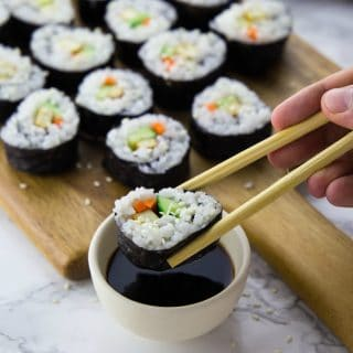 vegan sushi on a wooden board with one piece of sushi being dipped into a small bowl of soy sauce in the front