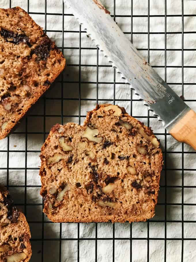 vegan banana bread on a cooling rack with a knife on the side