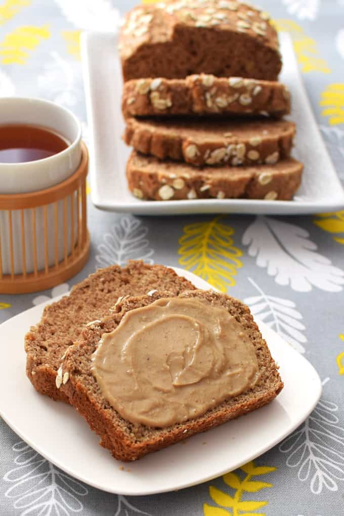 a slice of vegan banana bread on a small white plate with a cup of tea and more banana bread in the background